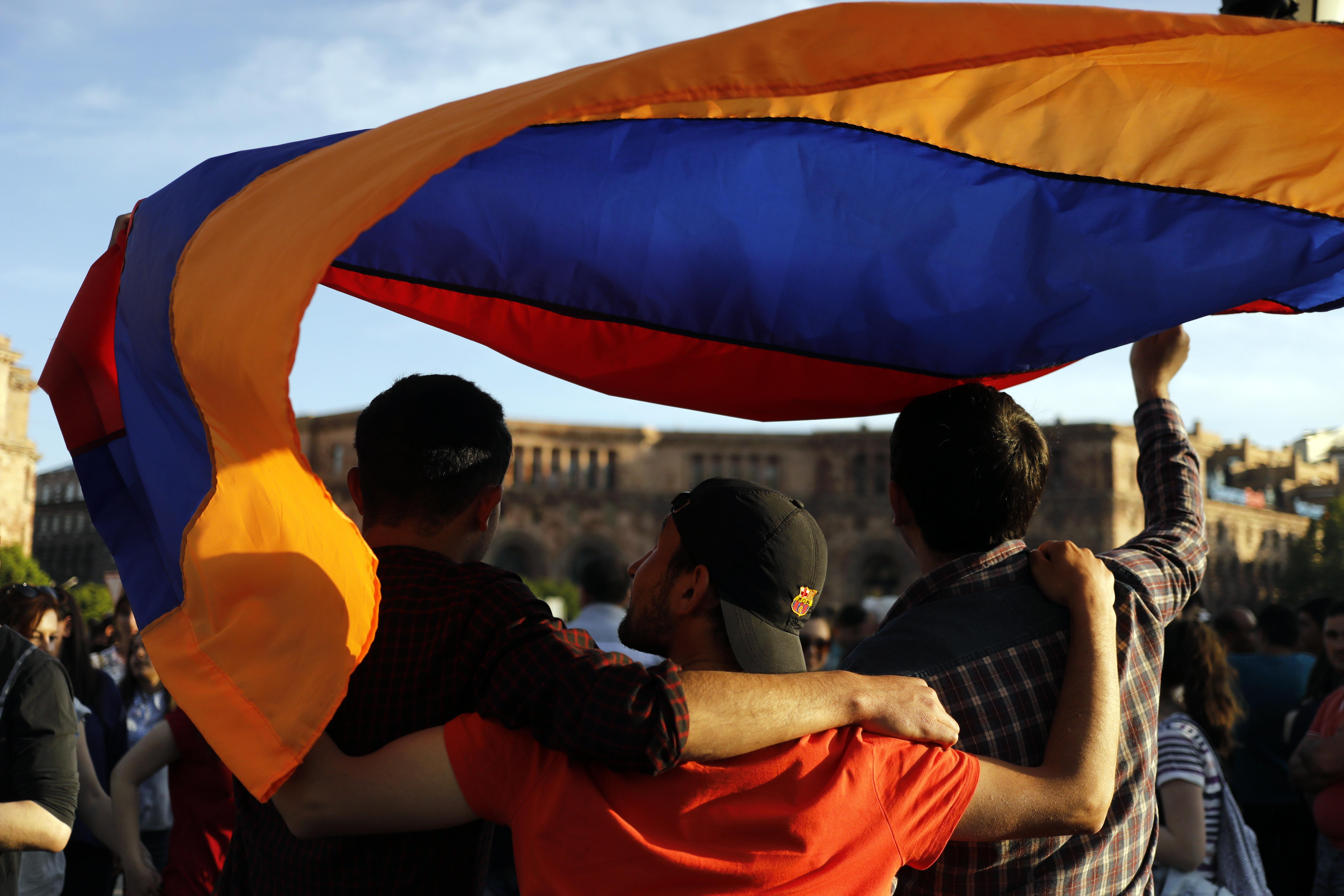"""YEREVAN, ARMENIA - MAY 2, 2018: Waving an Armenian flag at a rally in support of Nikol Pashinyan, one of the leaders of the 'Way Out' Alliance (Yelk) Party, in Yerevan's Republic Square as he fails to gain enough votes at the Armenian National Assembly to be elected prime minister. Artyom Geodakyan/TASS  Àðìåíèÿ. Åðåâàí. Ó÷àñòíèêè ìàññîâîé àêöèè â ïîääåðæêó ãëàâû îïïîçèöèîííîé ïàðëàìåíòñêîé ôðàêöèè """"Åëê"""" Íèêîëà Ïàøèíÿíà íà ïëîùàäè Ðåñïóáëèêè. Íàêàíóíå ðóêîâîäèòåëü îïïîçèöèîííîé ïàðëàìåíòñêîé ôðàêöèè """"Åëê"""" Í.Ïàøèíÿí ïðèçâàë çàáëîêèðîâàòü ðàáîòó àýðîïîðòîâ, ïåðåêðûòü âñå óëèöû è îáúÿâèòü òîòàëüíóþ çàáàñòîâêó â îòâåò íà ïðîâàë â ïàðëàìåíòå ãîëîñîâàíèÿ ïî âîïðîñó èçáðàíèÿ Í.Ïàøèíÿíà íà ïîñò ïðåìüåð-ìèíèñòðà ñòðàíû. Àðòåì Ãåîäàêÿí/ÒÀÑÑ"""